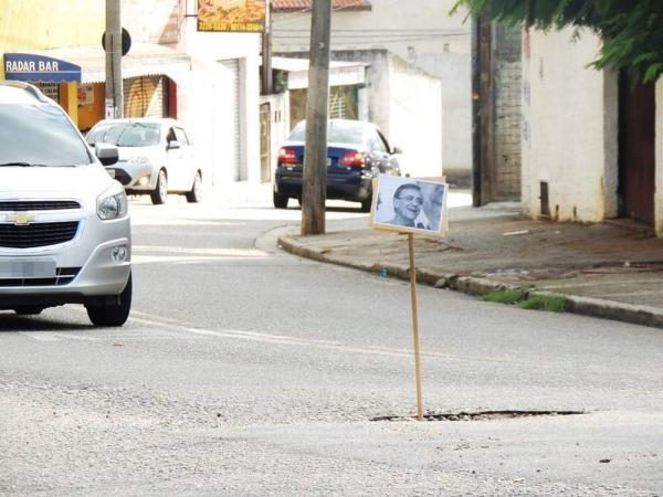 Moradores espalham placas com fotos do prefeito em buracos de rua
