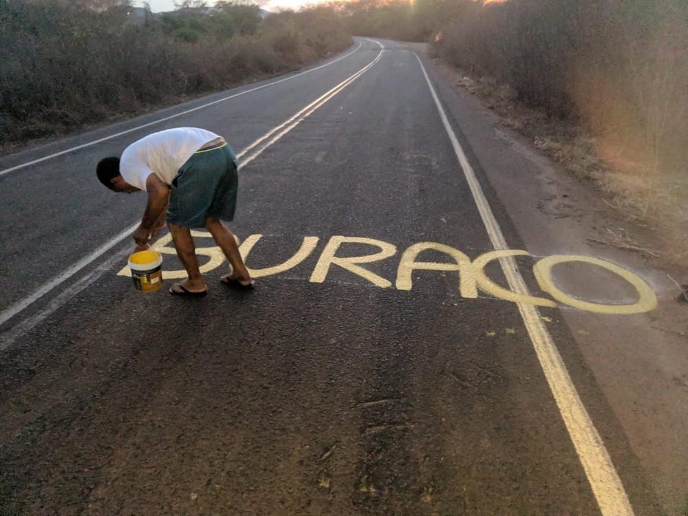 Morador pinta PI-141 com avisos para alertar condutores sobre buracos, em Canto do Buriti, Sul do Piauí